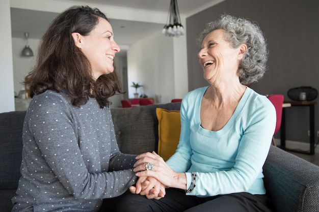 Positive elderly woman and her daughter chatting, laughing