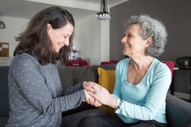 Positive elderly woman and her daughter chatting