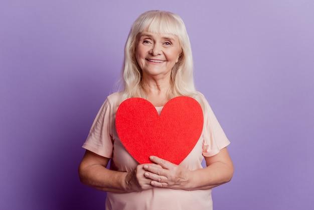 Позитивная пожилая женщина держит большую валентинку в форме сердца, изолированную на фиолетовом фоне