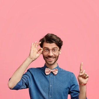 Positive elegant young male with trendy hairstyle and stubble, dressed in denim shirt with bowtie, has joyful expression, points upwards against pink wall, keeps hand on rim of spectacles