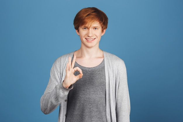 Positive emotion concept. close up of young handsome ginger cheerful guy in grey outfit smiling brightly, showing ok sign with hand,  with relaxed and happy expression.