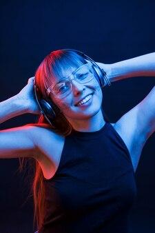 Положительные эмоции. студия снята в темной студии с неоновым светом. портрет молодой девушки