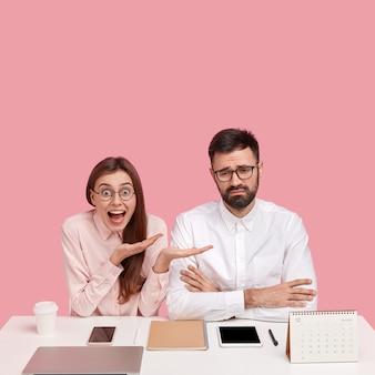 ポジティブな感情的な幸せな女性は、経済的な問題に直面している欲求不満の青年実業家に注目を集め、電子機器、コーヒー、メモ帳と一緒に白いデスクトップに座っています。チームワーク