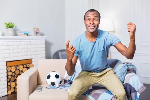 Положительный эмоциональный приятный мужчина улыбается и смотрит на экран телевизора, показывая свою поддержку футбольной команде