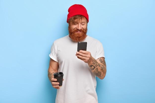 ポジティブな感情と現代のテクノロジーのコンセプト。陽気なスタイリッシュな男は赤い帽子と白いtシャツを着て、ワイヤレスインターネットに接続された携帯電話を介して友人と生姜ひげチャットをしていますコーヒーを飲みます
