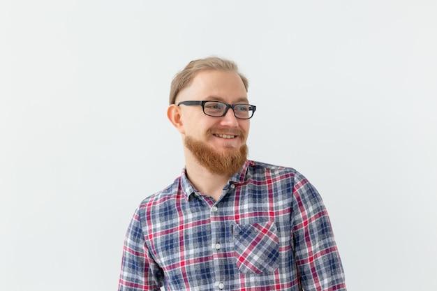 ポジティブな感情と人々の概念-眼鏡をかけた若いひげを生やした男は白い表面に笑っています