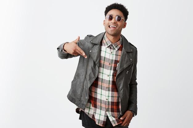 Позитивные эмоции. красивый молодой радостный темнокожий африканец с вьющимися волосами в модной черной кожаной куртке и коричневых очках, улыбающийся зубами, жестикулирующий рукой, увидев старую шкуру