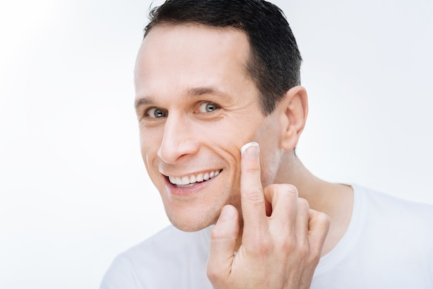 Позитивные эмоции. веселый милый довольный мужчина улыбается и наносит крем для лица, увлажняя его кожу