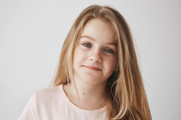 ポジティブな感情。幸せそうな表情で、長い光の髪と優しく笑って明るい青い目を持つ豪華な少女のクローズアップ。
