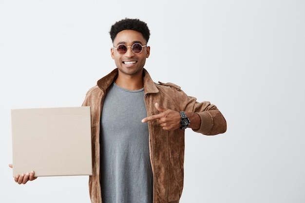 Positive emotions. close up of young good-looking afro american male student with curly hair in casual clothes and sun-glasses holding carton board, pointing at it with hand, smiling with teeth.