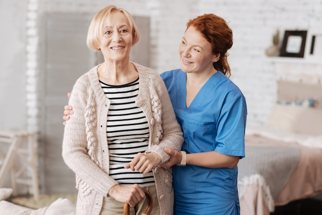 Positive emotions. competent supportive careful lady holding the elderly woman by her hands and assisting her taking a walk around her apartment