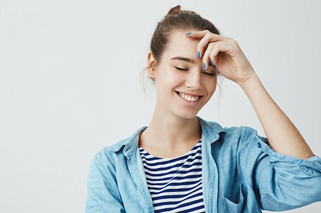 Concetto di emozioni positive. donna attraente con la mano della tenuta dell'acconciatura del panino sulla fronte mentre sorridendo con gli occhi chiusi, stanti. giovane artista che crea in mente un nuovo dipinto