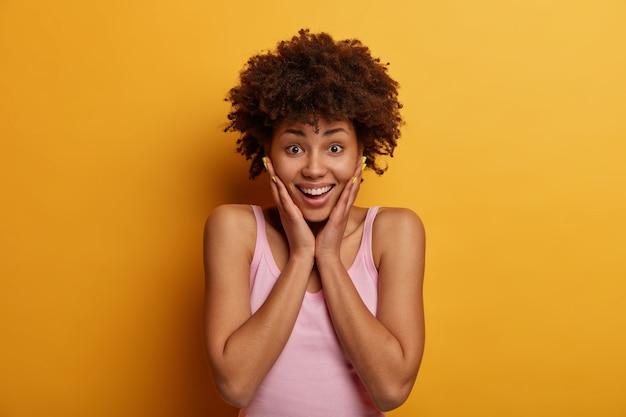 Concetto di emozioni positive. la donna afroamericana riccia e gioiosa tocca le guance, ha imparato qualcosa di inaspettato e fantastico, guarda con un sorriso felice, posa sul muro giallo