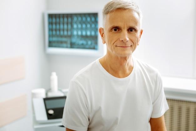 Позитивные эмоции. довольный милый пожилой мужчина сидит в кабинете врача и улыбается вам, находясь в хорошем настроении