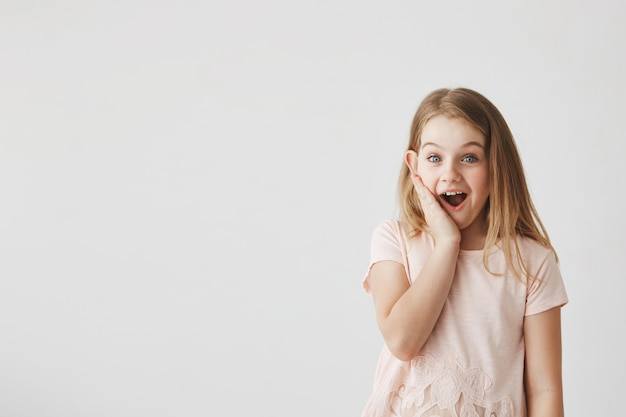 Positive emotions and expressions. cute little girl  with happy and excited expression, holding hand on cheek, being surprised to get flowers from boy.