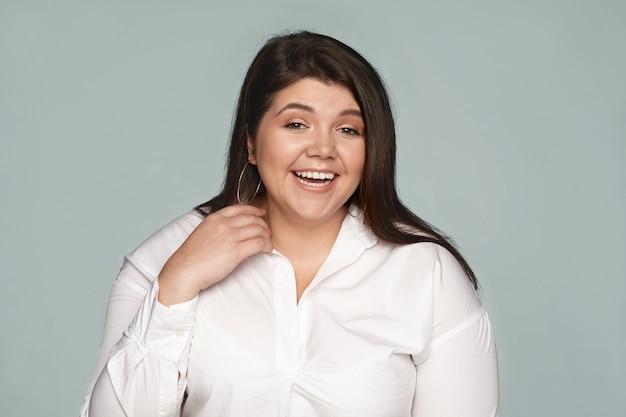 ポジティブな感情、感情、反応。冗談のポーズで笑っている緩い黒髪の美しい魅力的な若い女性従業員