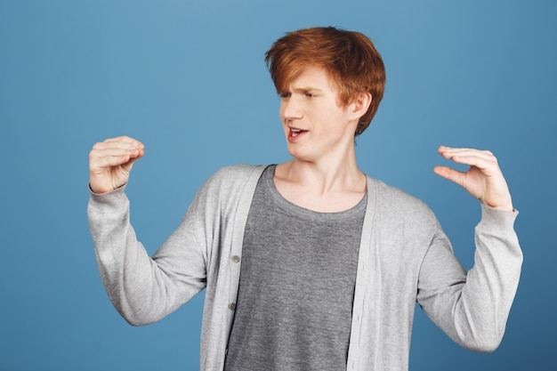 Positive emotions. funny young attractive ginger guy in gray t-shirt under cardigan talking to his hands, making silly face expressions, having fun, making little brother stop crying.