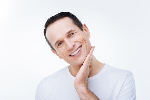 Позитивные эмоции. счастливый веселый довольный мужчина трогает его подбородок и улыбается, глядя на вас