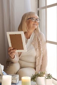 ポジティブな感情。写真を持って、素晴らしい気分で窓をのぞき込む幸せな陽気な年配の女性