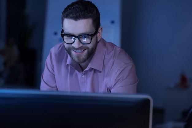 긍정적 인 감정. 컴퓨터 화면을보고 그의 일을 마치는 동안 웃고 행복 기쁘게 좋은 사람