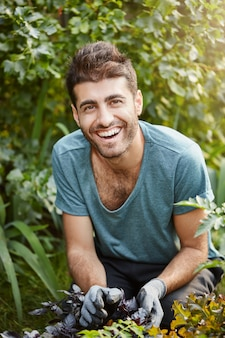 Positive emotions, healthy lifestyle. vertical close up outdoors portrait of young mature bearded caucasian male gardener in blue t-shirt smiling, working in garden,