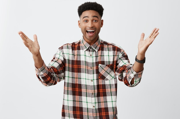 Positive emotions. isolated portrait of young happy tan-skinned guy with afro haircut in long-sleeved checkered shirt spreading hands, being excited to see old friend after vacation.