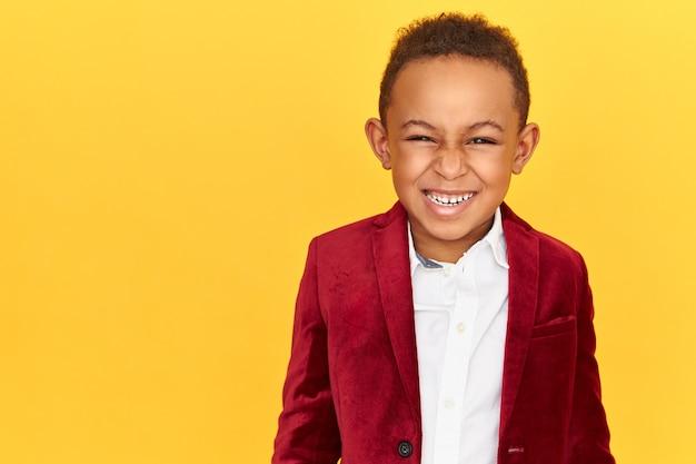 Emozioni positive, gioia e concetto di infanzia felice. bambino maschio dalla pelle scura allegro bello in giacca di velluto cremisi di buon umore, che guarda l'obbiettivo con un sorriso radioso, che mostra i denti bianchi