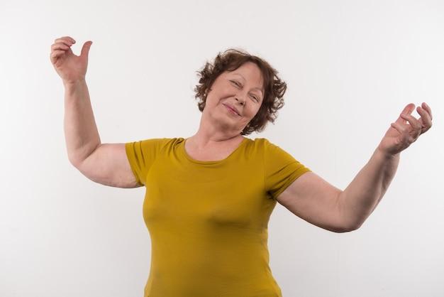 Позитивные эмоции. радостная пожилая женщина жестикулирует руками, чувствуя себя счастливой
