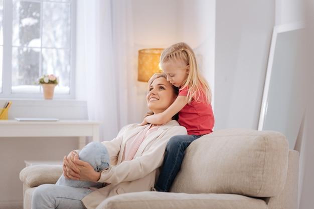 긍정적 인 감정. 즐거운 좋은 긍정적 인 어머니는 소파에 앉아 딸에게 안기면서 웃고 있습니다.