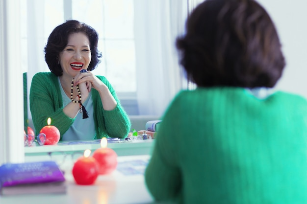 Positive emotions. joyful positive woman smiling to her reflection while being in a great mood