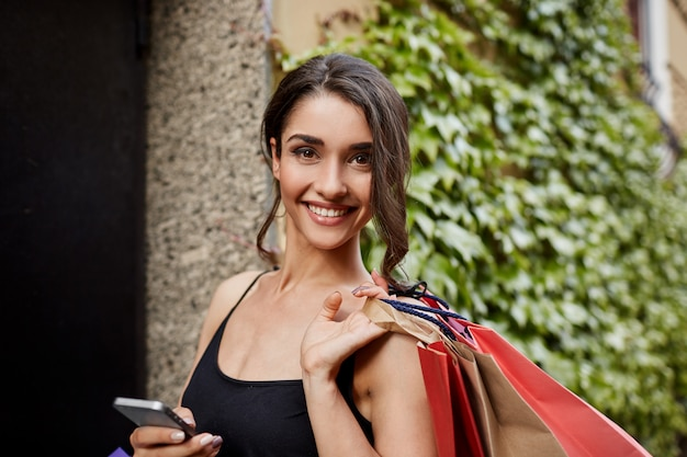 Positive emotions. lifestyle concept. close up portrait of beautiful joyful dark-haired caucasian woman in black shirt smiling with teeth, looking in camera with happy and relaxed expression, holding