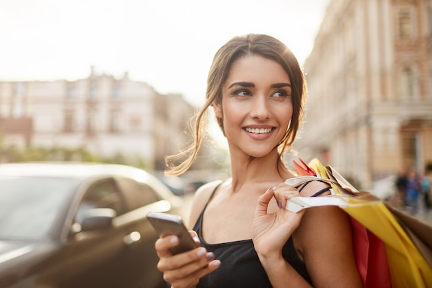 Positive emotions. lifestyle concept. close up of young charming dark-haired caucasian woman in black dress smiling with teeth, looking aside with relaxed expression, chatting with boyfriend on phone,