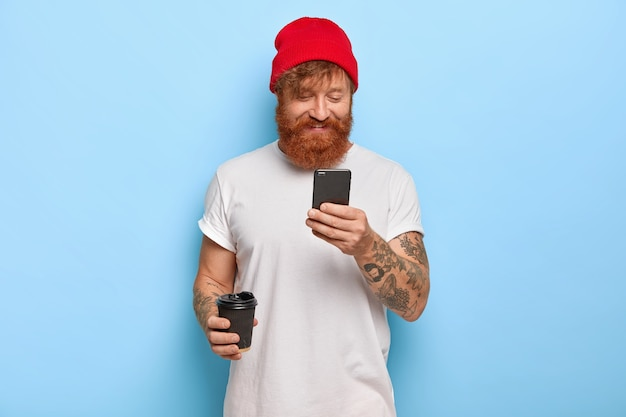Positive emotions and modern technologies concept. cheerful stylish man wears red hat and white t shirt, has ginger beard chats with friends via cell phone connected to wireless internet drinks coffee