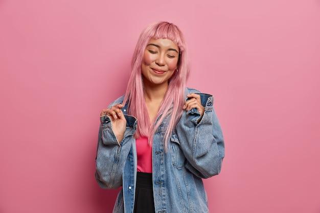긍정적 인 감정, 사람 및 패션 개념. 분홍색 긴 머리를 가진 기쁜 젊은 여자를 웃고, 눈을 감고, 새 데님 재킷을 구입하게되어 행복하며, 실내 스탠드