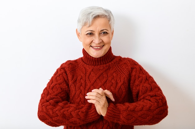 Positive emotions, reaction and feelings. portrait of attractive cheerful elderly senior lady with short gray hairstyle going to burst out laughing, being in good mood, holding hands in namaste