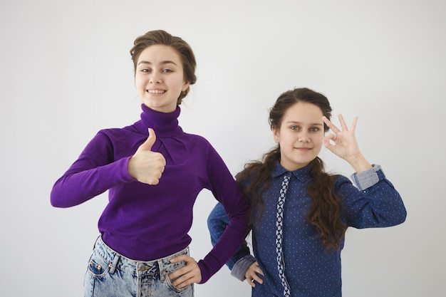 ポジティブな感情、サイン、ジェスチャーのコンセプト。あなたに何かを勧める2人の美しい陽気な白人姉妹