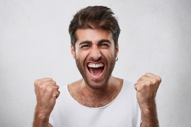 Positive emotions, victory, triumph, happiness concept. happy man with beard dressed in casual white t-shirt clenching his fists while rejoicing his victory of game posing over white