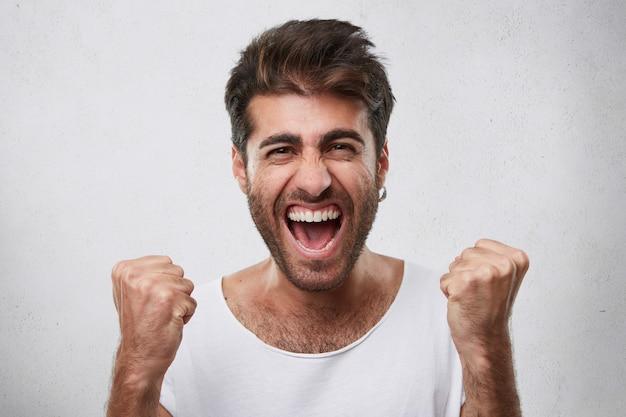 Положительные эмоции, победа, триумф, концепция счастья. счастливый человек с бородой, одетый в повседневную белую футболку, сжимает кулаки, радуясь своей победе в игре, позирующей над белым