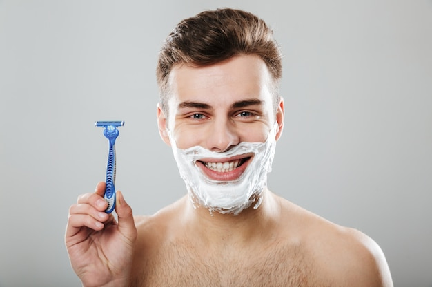 Positive emotions of young attractive guy during shaving with razor in bathroom putting cream on face over grey wall
