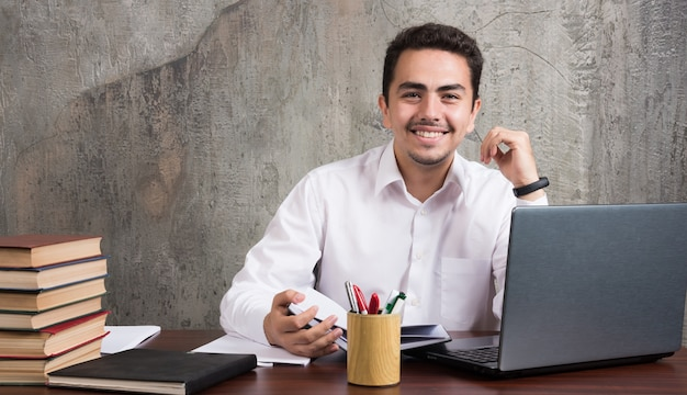 机に座ってノートを持っている前向きな従業員。高品質の写真
