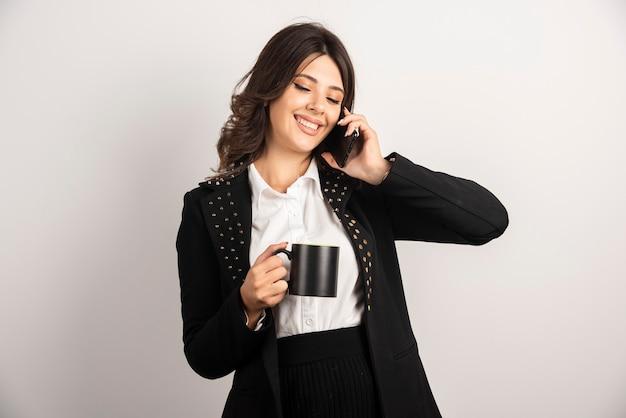 お茶を飲みながら電話で話す前向きな従業員