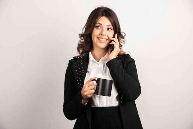Impiegato positivo che parla al telefono mentre tiene il tè