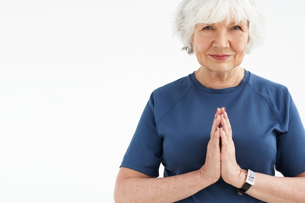 Positive energetic elderly woman with gray hair choosing active healthy lifestyle, smling, holding hands in namaste while practicing yoga or meditation