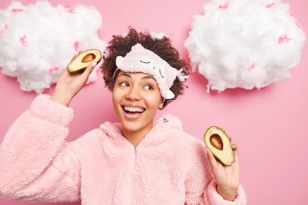 La donna energica positiva vestita in pigiama tiene metà dell'avocado per fare sorrisi cosmetici naturali ampiamente isolati sul muro rosa nuvole bianche sopra