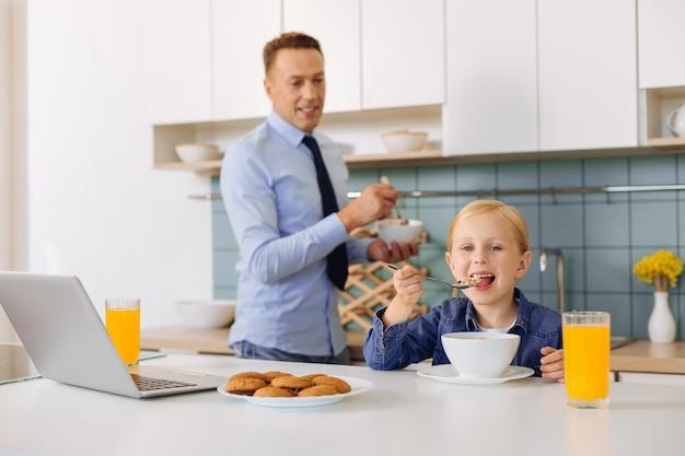 긍정적 인 정력 어린 소녀 테이블에 앉아 시리얼을 먹는