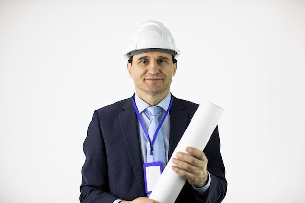 Positive engineer constructor in helmet formal clothing holds rolled-up drawing