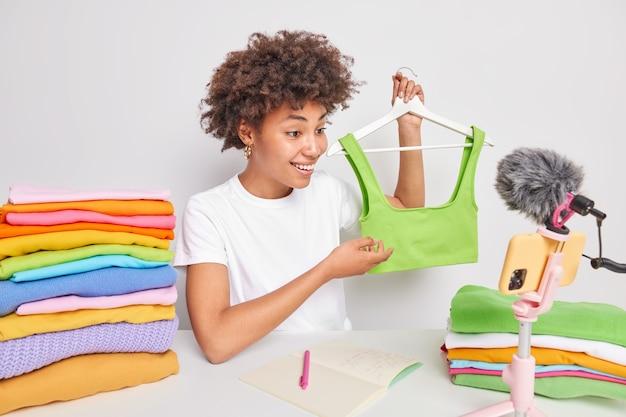 긍정적인 민족 여성 콘텐츠 제작자는 마지막 패션 의류를 광고하며 녹색의 세련된 탑 온라인 촬영 브랜드 광고 프로모션을 통해 자신의 패션 블로그에서 옷장 관리 과정을 만듭니다.