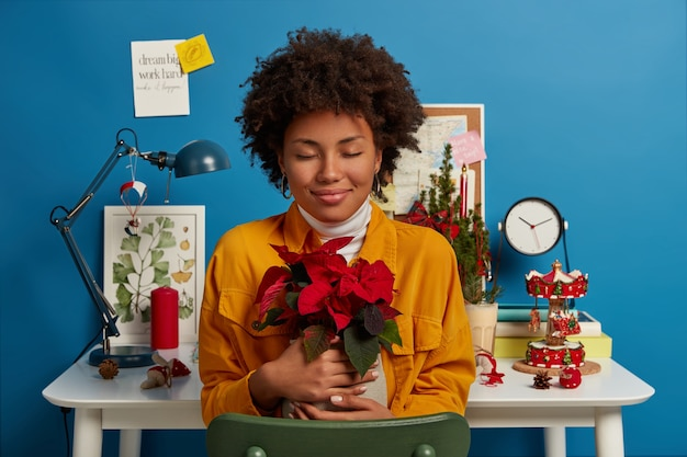 Positive ethnic girl enjoys pleasure from being at home, embraces vase with red beautiful flower, wears yellow denim jacket, poses over desktop and cozy decorated interior