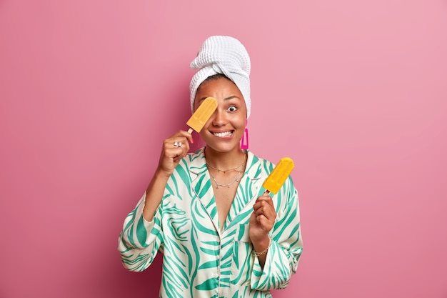 Positive ethnic housewife with dark skin covers eye with tasty cold ice cream has fun while eating delicious sweet dessert wears domestic clothes wrapped bath towel on head. summer time concept