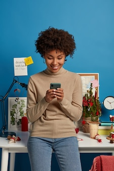 Positive ethnic woman blogger reads comments in blog, enjoys online communication, uses modern cellular, stands in coworking space, wears turtleneck and jeans, watches video in social networks